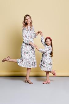 Linda mãe e filha em vestidos idênticos dançando no estúdio
