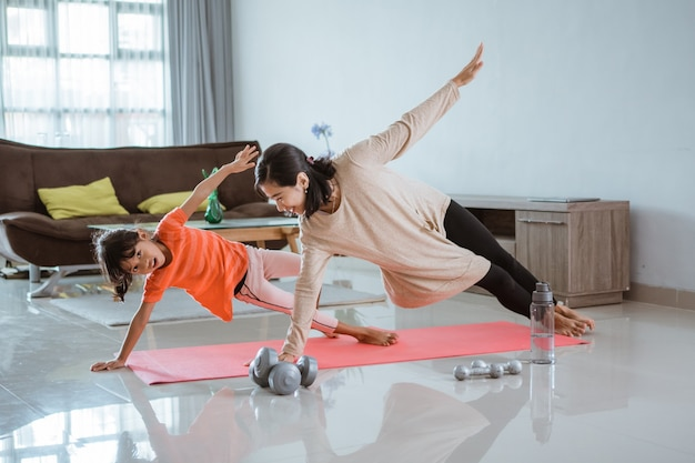 Linda mãe e filha fazendo exercícios esportivos em casa com a filha dela juntas