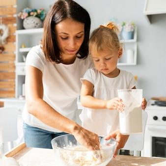 Linda mãe e filha linda cozinhando juntos