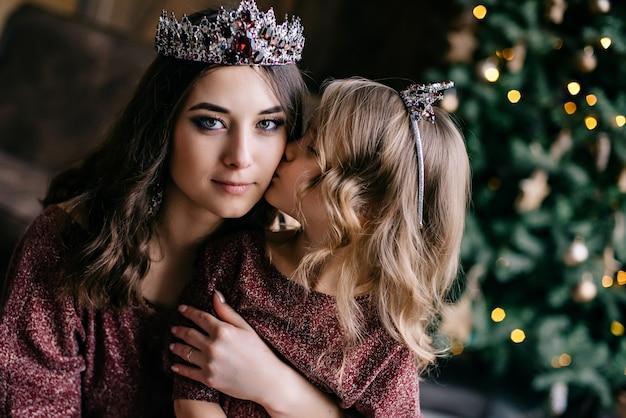 Linda mãe e filha na imagem da rainha e da princesa no vestido cor de marsala com cauda longa no loft
