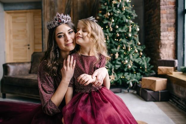 Linda mãe e filha na imagem da rainha e da princesa no vestido cor de marsala
