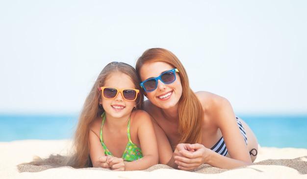 Linda mãe e filha na praia tropical