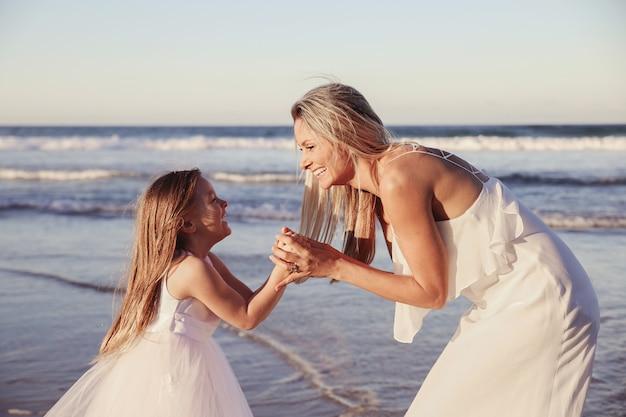 Linda mãe e filha rindo juntos na praia