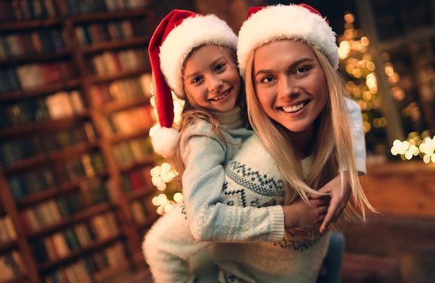 Linda mãe e filha, tem chapéus de natal, luzes da árvore de natal. férias do retrato. fundo de inverno. retrato de família de crianças. decoração de ano novo.