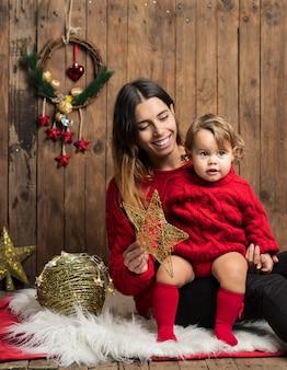 Linda mãe e filha vestidas da mesma forma com pulôveres vermelhos em fundo de madeira de natal
