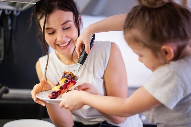 Linda mãe e jovem compartilhar bolo