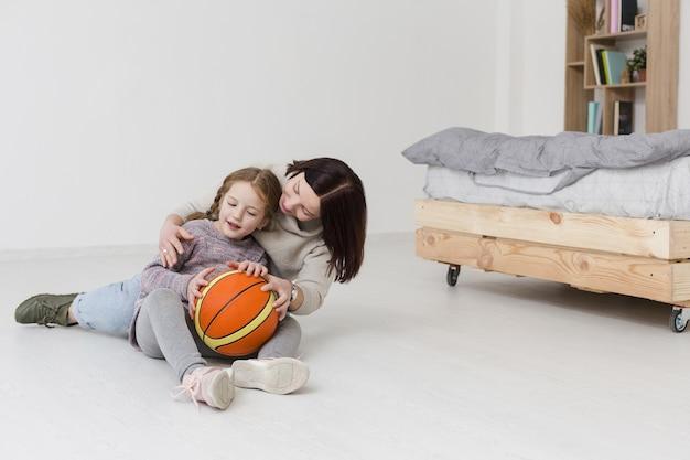 Linda mãe e menina desfrutando dentro de casa
