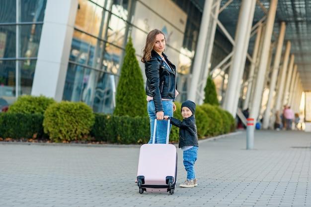 Linda mãe e sua filha bonita e elegante caminhar juntos e puxar uma mala rosa para o aeroporto.
