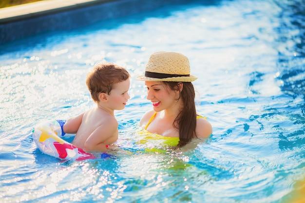 Linda mãe em um maiô amarelo e chapéu nada na piscina com o filho em um anel de borracha