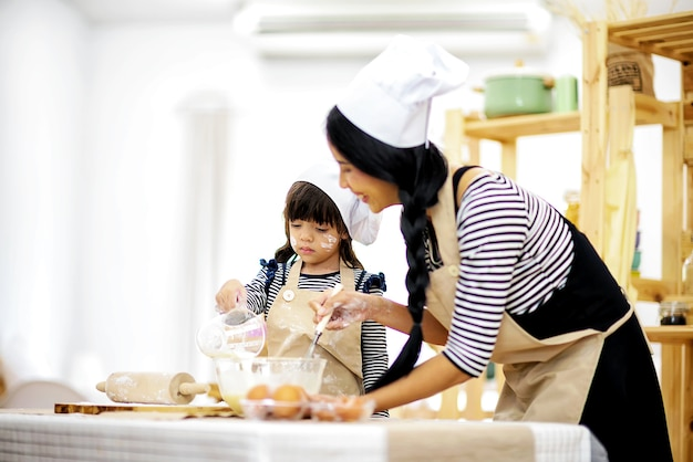 Linda mãe ensina sua filha enxada para preparar o café da manhã na cozinha
