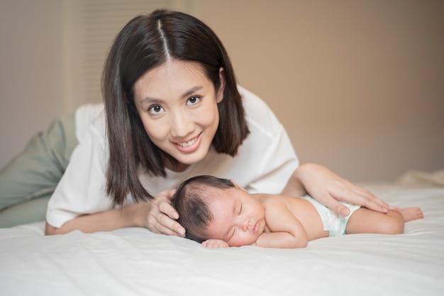 Linda mãe está brincando com seu bebê recém-nascido no quarto.
