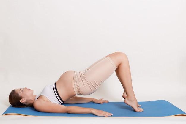 Linda mãe expectante fazendo yoga em casa