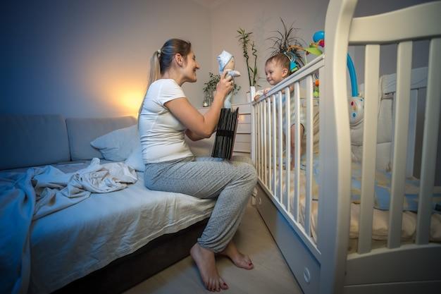 Linda mãe feliz brincando com seu filho no berço à noite Foto Premium