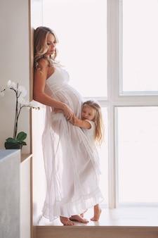 Linda mãe grávida com criança posando perto de uma janela em casa