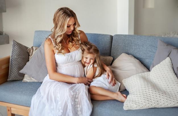 Linda mãe grávida sentada no sofá azul com a filha e olhando para ela enquanto a menina sorria
