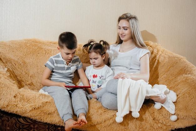 Linda mãe grávida sentada no sofá com seu filho e filha e jogando tablet