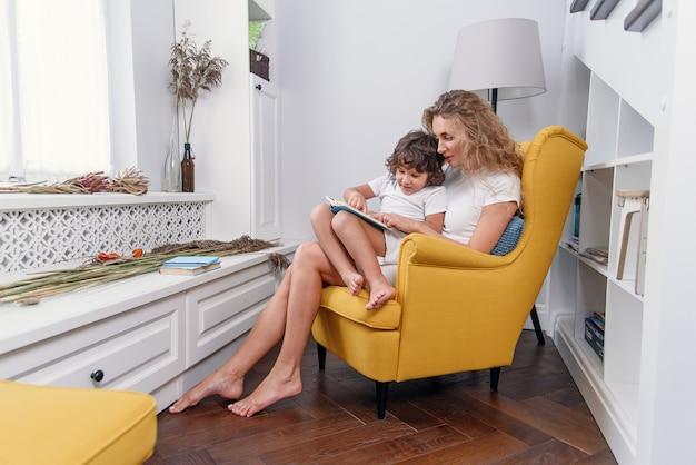 Linda mãe lê livro infantil para seu filho pequeno enquanto está sentado na confortável cadeira amarela perto da janela na casa aconchegante.