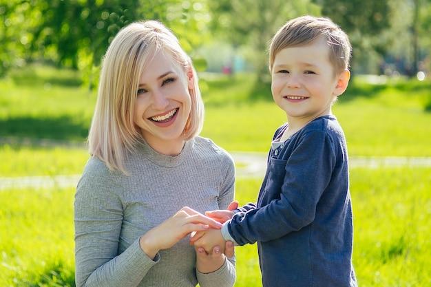 Linda mãe limpa as mãos com guardanapos do lindo bebê (filho) no parque, em um fundo de grama verde e árvores