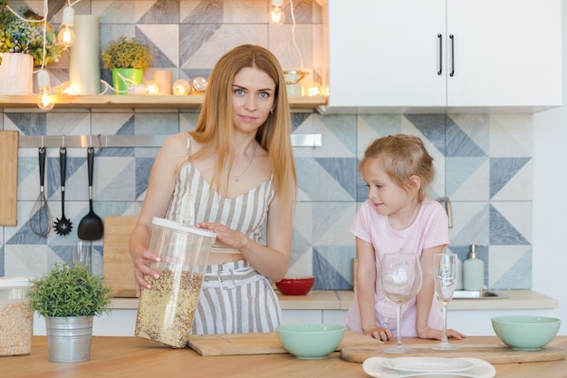 Linda mãe loira e linda filha se divertindo e brincando em um apartamento moderno com um design elegante