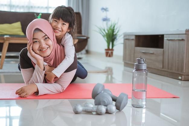 Linda mãe muçulmana e filha treinam juntas para ficarem saudáveis. família mulher e criança gostam de se exercitar em casa