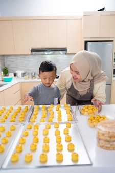 Linda mãe muçulmana fazendo bolo com o filho em casa juntos