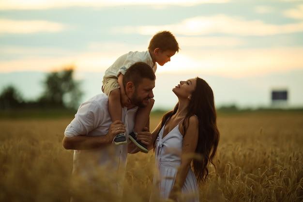 Linda mãe, pai e seu filhinho fofo se divertem juntos e sorriem lá fora