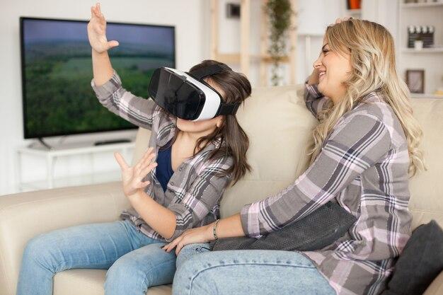 Linda mãe rindo enquanto a filha está jogando jogos usando fone de ouvido de realidade virtual.