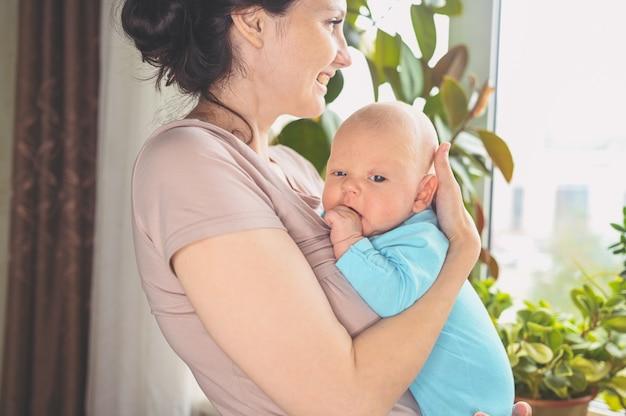 Linda mãe segurando nos braços seu lindo filho recém-nascido