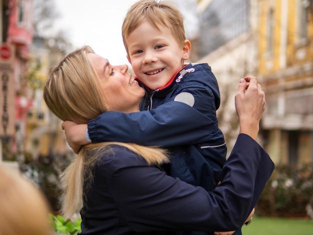 Linda mãe segurando seu filho ao ar livre