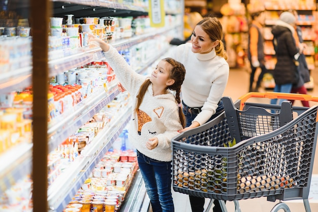 Linda mãe segurando uma cesta de supermercado com o filho caminhando no supermercado