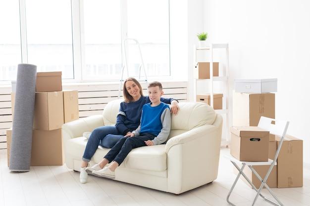 Linda mãe solteira e filho filho relaxando após a mudança. o conceito de hipoteca de inauguração e a alegria de uma nova moradia.