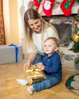 Linda mãe sorridente e seu filho bebê com um presente de natal no chão da sala de estar