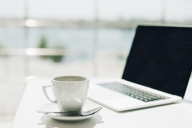 Linda manhã xícarade café perto de computador portátil no café.