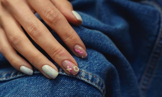 Linda manicure feminina de verão em fundo de jeans
