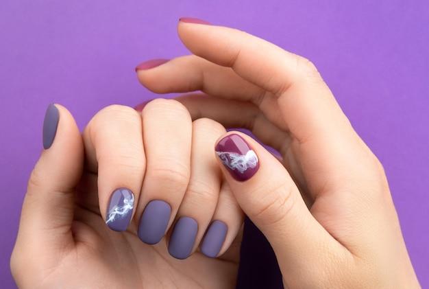 Linda manicure roxa cor de vinho fosca em fundo criativo. desenho de unhas na moda primavera verão.