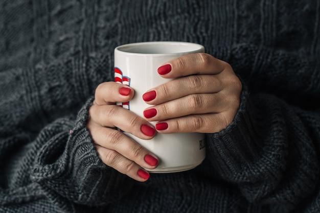Linda manicure vermelha com uma xícara de chá