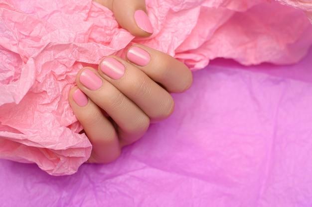 Linda mão feminina com esmalte rosa perfeito, segurando um papel rosa na superfície rosa.