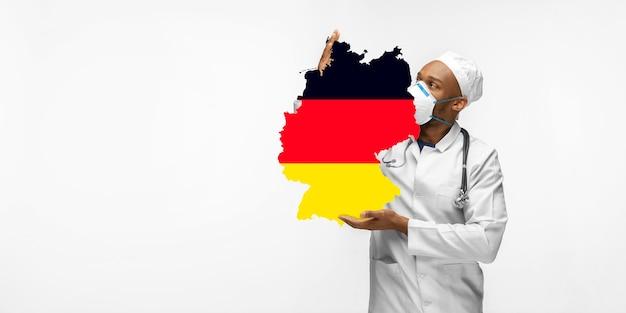 Linda médica afro-americana se preocupa com a alemanha sobre o fundo branco do estúdio. copyspace. conceito de saúde e medicina, cuidando, tratamento, diagnóstico durante o surto de coronavírus. Foto Premium