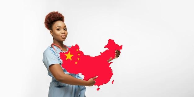 Linda médica afro-americana se preocupa com a china isolada sobre o fundo branco do estúdio. copyspace. conceito de cuidados de saúde e medicina, cuidar, tratamento durante o surto de coronavírus, pandemia.