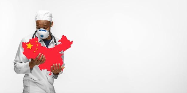 Linda médica afro-americana se preocupa com a china sobre o fundo branco do estúdio. copyspace. conceito de saúde e medicina, cuidando, tratamento, diagnóstico durante o surto de coronavírus.
