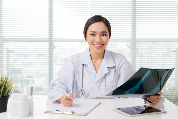 Linda médica asiática examinando relatório de radiografia na clínica