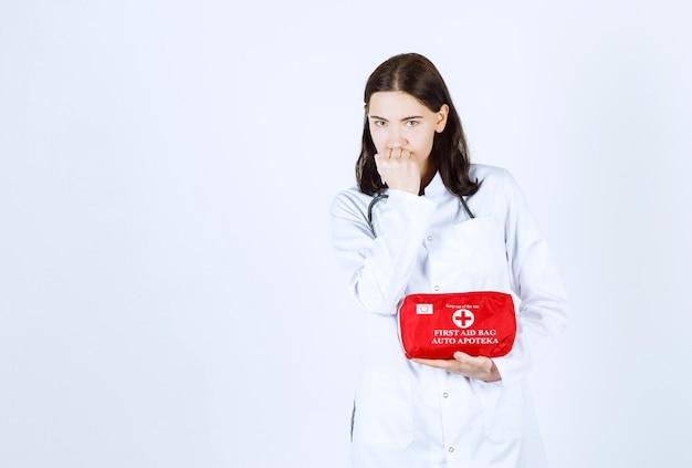 Linda médica colocando a mão perto da boca enquanto segura sua maleta de médico