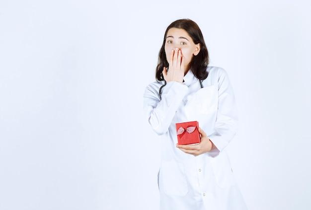 Linda médica com um jaleco fechando a boca e segurando seu presente na frente da parede vermelha