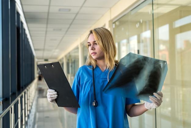 Linda médica de uniforme azul, olhando para um filme de raio-x dos pulmões. covid19