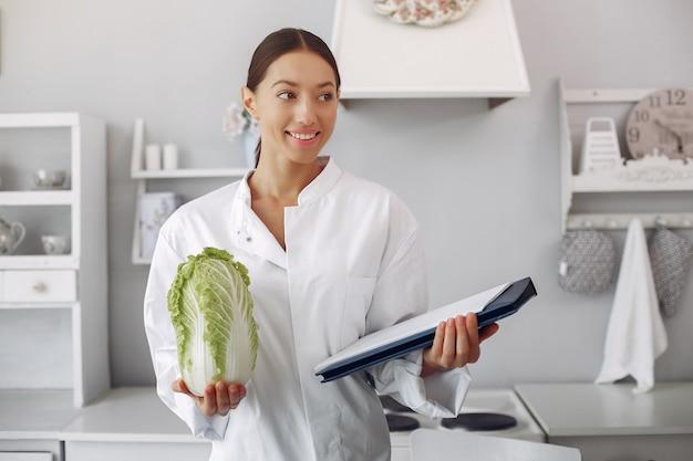 Linda médica em uma cozinha com legumes