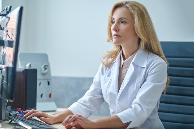 Linda médica loira focada em verificar seu e-mail