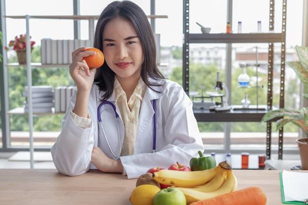 Linda médica mostrando uma laranja no escritório
