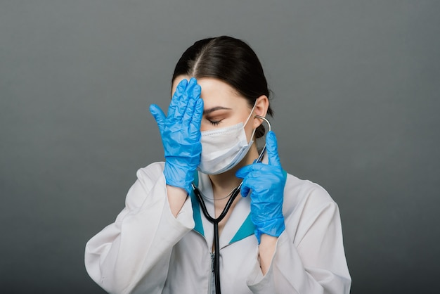 Linda médica segurando o estetoscópio e sorrindo isolado em cinza.