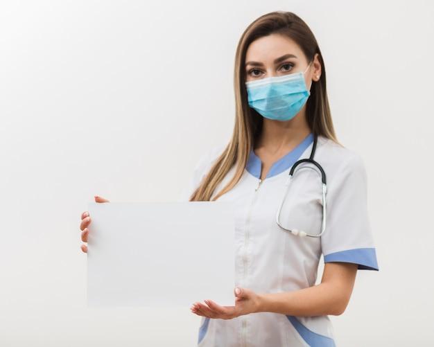 Linda médica segurando um cartão em branco