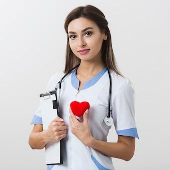 Linda médica segurando um coração de pelúcia